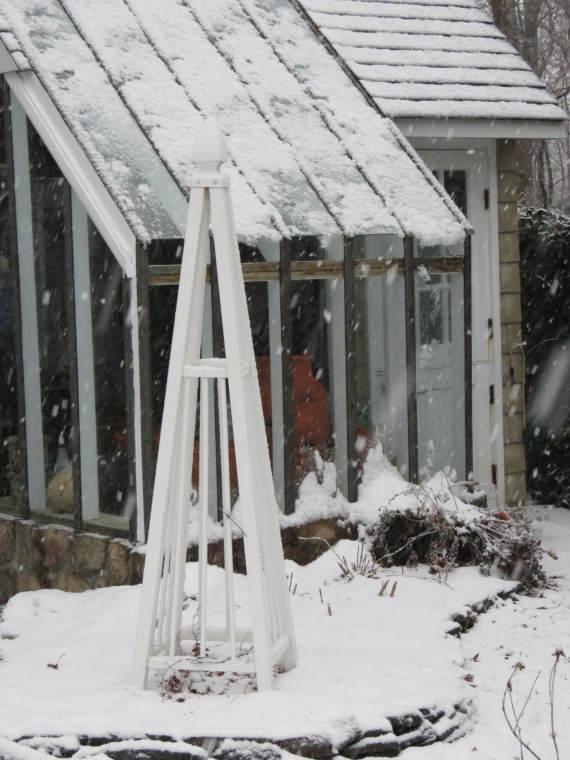 Snow falling on the potting shed.